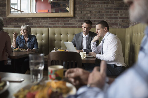 Businessmen working at laptop at diner table - HEROF23607