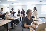College students studying and talking in classroom - HEROF23613