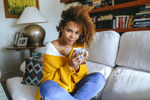Portrait of attractive young woman with curly hair holding mug at home - KIJF02280