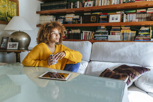 Thoughtful young woman with curly hair holding mug at home - KIJF02283