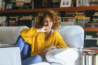 Portrait of young woman with curly hair sitting on sofa at home - KIJF02286