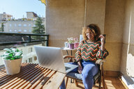 Young woman with curly hair sitting on balcony using laptop - KIJF02292