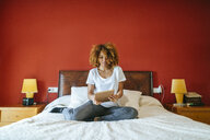 Young woman with curly hair sitting on bed using tablet - KIJF02298