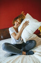 Young woman with curly hair sitting on bed at home holding pillow - KIJF02307