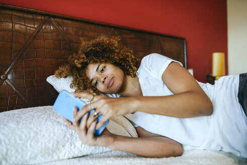 Young woman with curly hair lying in bed at home using cell phone - KIJF02310