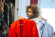 Young woman with curly hair at home looking at clothing in her wardrobe - KIJF02322
