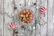 Walnuts on a plate with Christmas decoration, overhead view - LVF07799