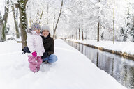 Happy mother with daughter at a moat in winter landscape - DIGF05870