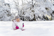 Cute little girl playing with snow in winter - DIGF05885