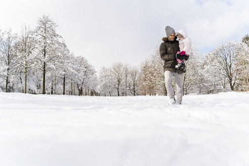 Father carrying daughter walking in winter landscape - DIGF05894