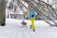 Happy mother with daughter on sledge in winter landscape - DIGF05900
