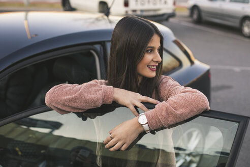 Smiling teenage girl leaning on car door looking at distance - ACPF00469