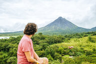 Costa Rica, Man looking towards the Arenal Volcano - KIJF02325