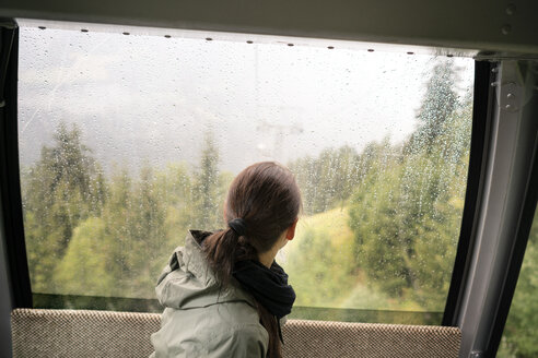 Switzerland, Valais, woman in a cable car looking out of rainy window - DMOF00109