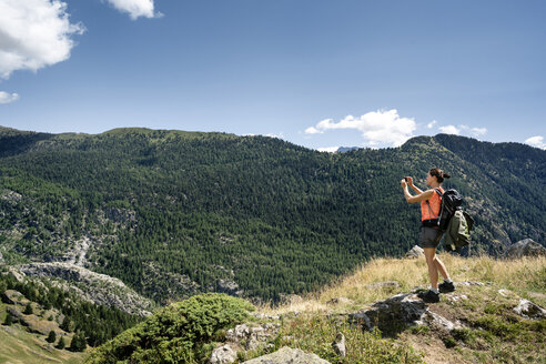 Switzerland, Valais, woman taking picture during a hiking trip in the mountains from Belalp to Riederalp - DMOF00112