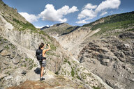 Switzerland, Valais, woman taking picture during a hiking trip in the mountains at Aletsch Glacier - DMOF00115