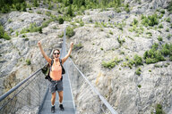 Switzerland, Valais, cheering woman on a hiking trip in the mountains from Belalp to Riederalp on a swinging bridge - DMOF00118