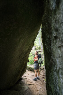 Switzerland, Valais, woman on a hiking trip on the Massaweg at a rock passage - DMOF00124
