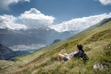 Switzerland, Valais, woman on a hiking trip in the mountains towards Foggenhorn lying on alpine meadow - DMOF00130