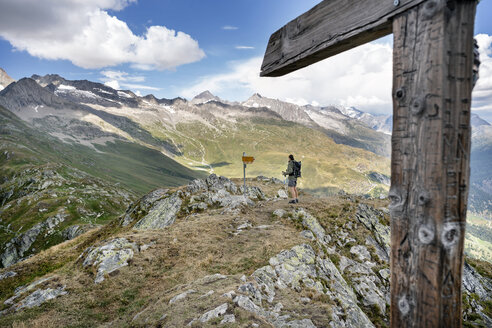 Switzerland, Valais, woman on a hiking trip in the mountains at Foggenhorn summit - DMOF00133