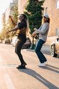 Full length of smiling friends dancing on road at city - MASF11367