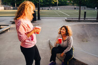 Smiling young women talking while having drinks at skateboard park - MASF11370