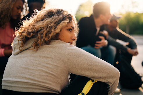 Thoughtful woman sitting with friends at skateboard park - MASF11376
