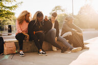 Multi-ethnic friends looking at smart phone while sitting at skateboard park - MASF11379