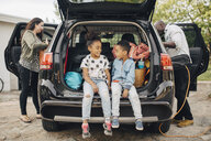 Full length of smiling siblings sitting on car trunk with parents standing in front yard - MASF11427
