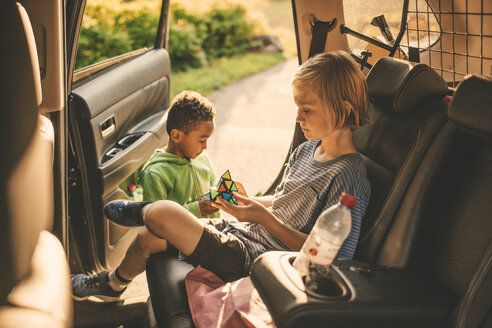 Girl playing puzzle cube while sitting in car by brother at park - MASF11433