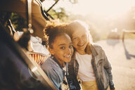 Portrait of smiling multi-ethnic girls in car trunk during picnic - MASF11436