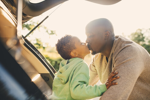 Father kissing son sitting in car trunk - MASF11439