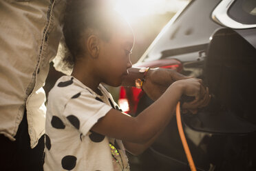 Midsection of man assisting daughter in charging electric car on driveway - MASF11445