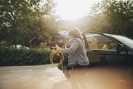 Woman holding electric plug by car on driveway - MASF11451