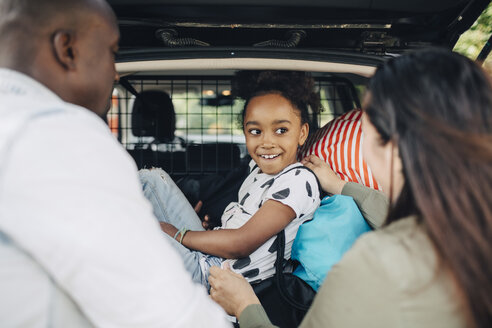 Smiling girl looking at mother standing by father while sitting on luggage in car trunk - MASF11460