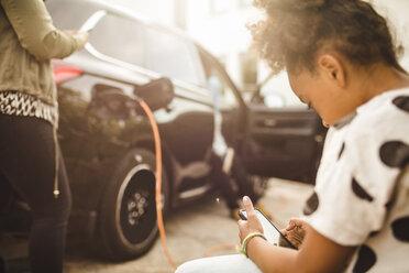 Girl using smart phone while sitting in yard - MASF11463