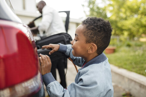 Side view of boy looking while charging electric car - MASF11469