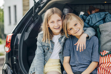Portrait of smiling blond girl sitting with arm around sister in car trunk against house - MASF11472