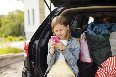 Blond girl using smart phone while sitting in electric car trunk - MASF11475