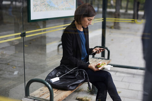 Mid adult businesswoman using smart phone while eating sandwich at bus stop in city - MASF11478