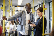 Multi-ethnic commuters sharing smart phone while standing in tram - MASF11484