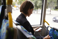 Mid adult businesswoman using smart phone while sitting in bus - MASF11490