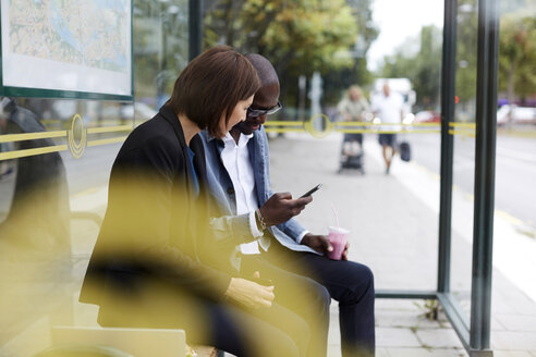 Multi-ethnic commuters sharing smart phone while sitting at bus stop in city - MASF11496