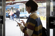 Businesswoman using smart phone while standing in railroad station - MASF11499