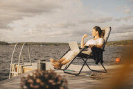 Full length of woman with laptop talking through headphones while sitting on jetty against sky - MASF11511