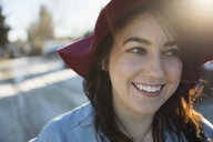 Close up smiling young brunette woman in red fedora looking away - HEROF23652