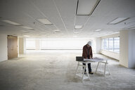 Contractor reviewing blueprints in unfinished, empty open plan office - HEROF23682