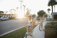 Couple riding beach cruiser bicycles on summer sidewalk - HEROF23760