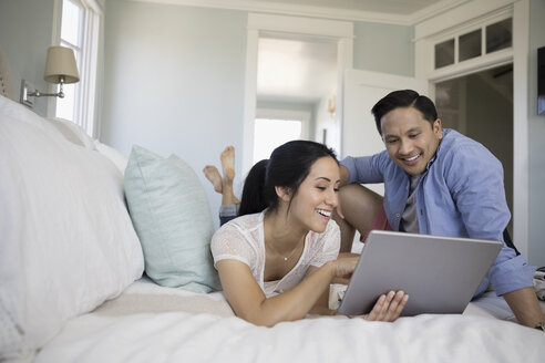 Couple using digital tablet on bed - HEROF23769