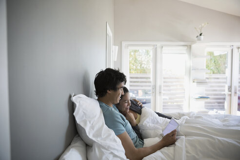 Couple relaxing, using digital tablet on bed - HEROF23790